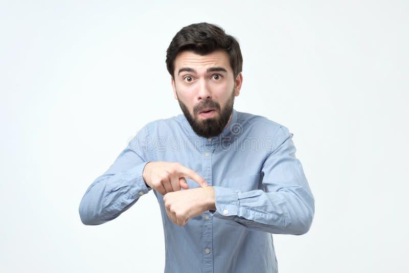 De ongelukkige bedrijfsmens in blauw overhemd verloor zijn horloge stock afbeelding