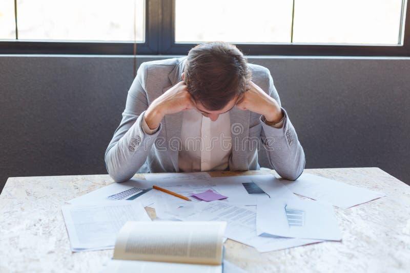 De ongelukkige man zit bij het bureau met documenten, gek overhellend zijn hoofd Binnen in het bureau royalty-vrije stock foto's