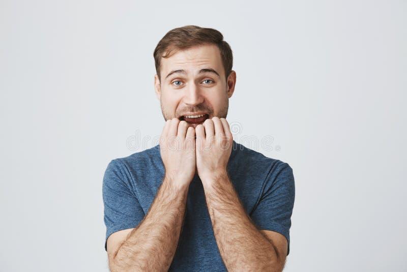 De ongelukkige ongerust gemaakte droevige mens met baard in blauwe t-shirt klemt tanden dicht, bijt spijkers, is bang om slecht n royalty-vrije stock afbeelding