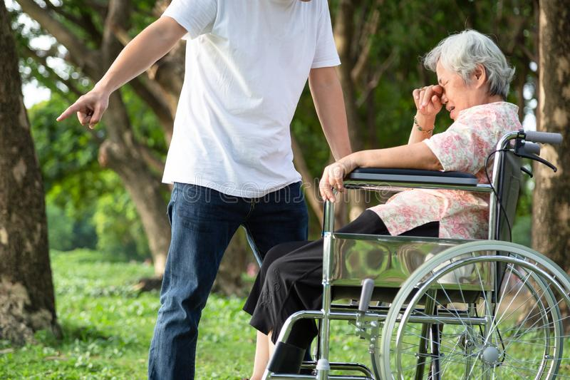 De ongelukkige, problemen Aziatische familie, de boze mens of de mannelijke verzorger verdreven zijn bejaarde in rolstoel ruzie,  stock foto