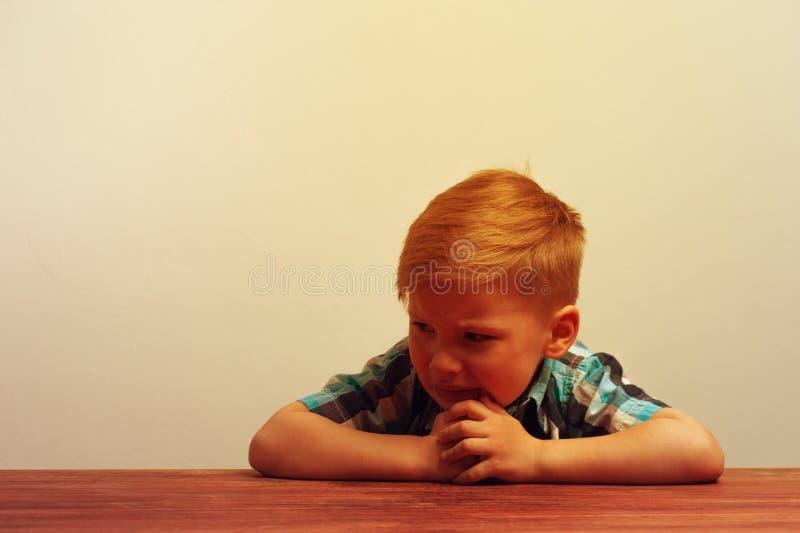 De ongelukkige zitting van het caucasinkind bij de lijst stock afbeeldingen