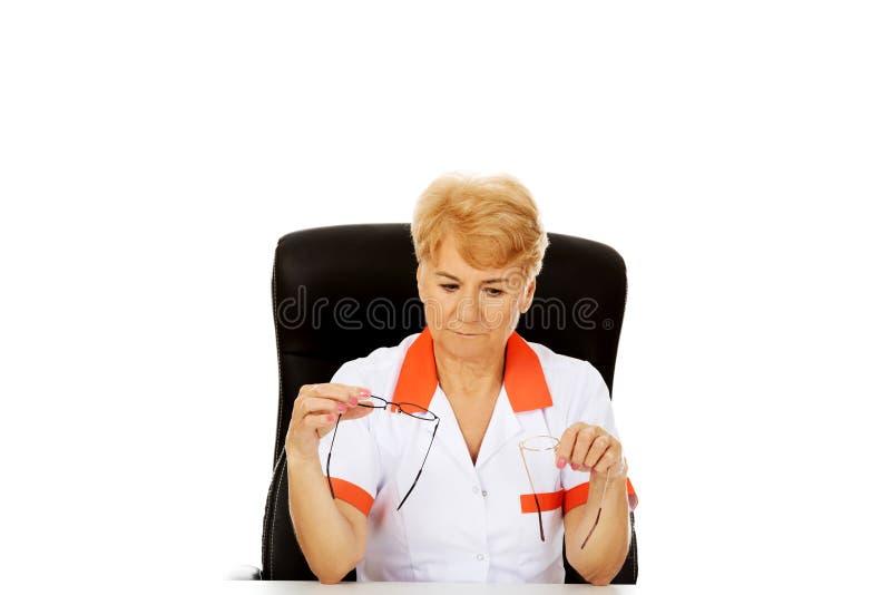 De ongerust gemaakte bejaarde vrouwelijke arts of verpleegster zitting achter het bureau en houdt twee paar glazen stock fotografie