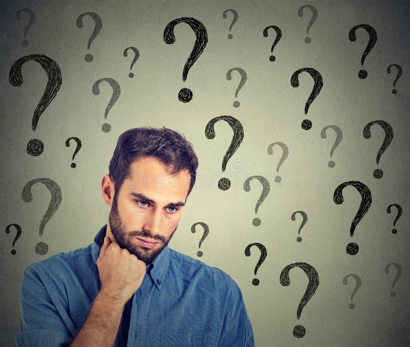 De ongerust gemaakte droevige mens heeft vele vragen neer kijkend stock afbeelding