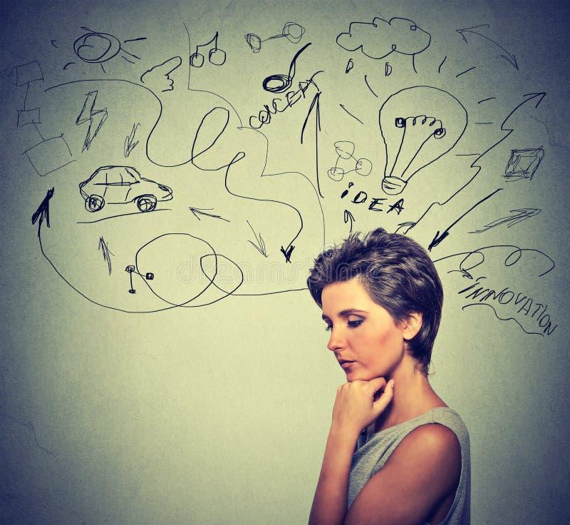 De ongerust gemaakte jonge vrouw die het dromen denken heeft vele ideeën neer kijkend stock afbeeldingen