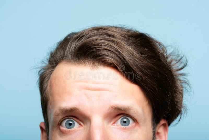 De ongerust gemaakte zenuwachtige gealarmeerde mens kijkt piepgeluid uit bodem royalty-vrije stock afbeelding