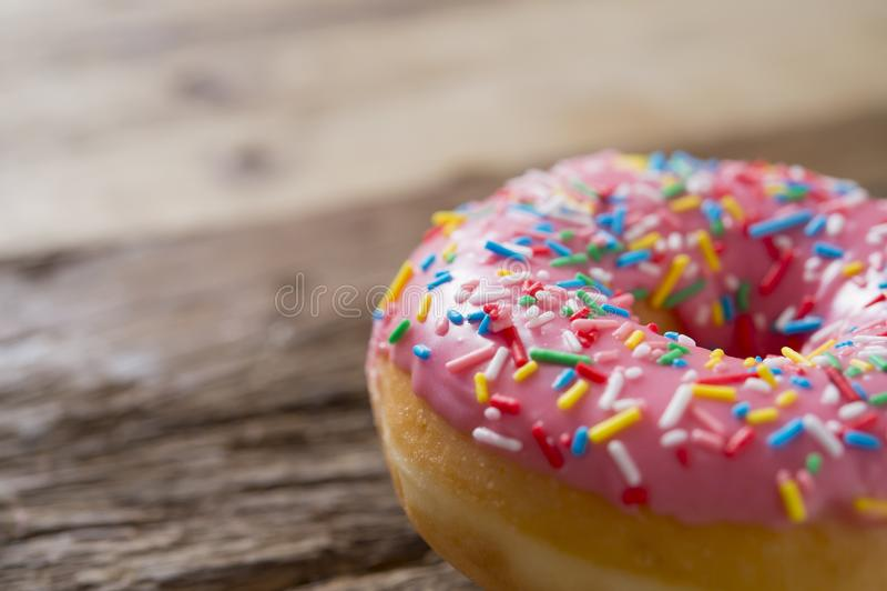De ongezonde maar heerlijke zoete cake van de suikerdoughnut op uitstekende houten lijst in de gezondheidszorg van de levensstijl stock foto
