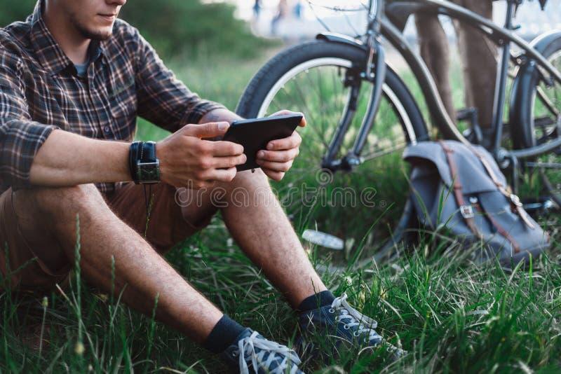 De onherkenbare Jonge Reizigersmens zit op de Zomerweide dichtbij Fiets, Holding en het Bekijken Tablet Rustende Reis royalty-vrije stock afbeeldingen