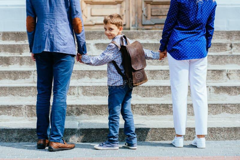 De onherkenbare ouders nemen kind aan school De leerling van lage school gaat studie met rugzak Achtermening van vader, moeder royalty-vrije stock foto's