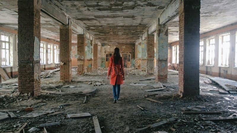 De onherkenbare vrouw in een rode mantel inspecteert de vernietigde bouw na de rampenaardbeving, vloed, brand royalty-vrije stock afbeelding