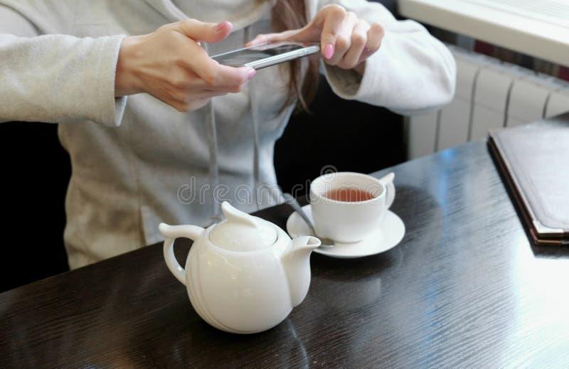 De onherkenbare vrouw ` s overhandigt beelden van theepot en Kop in een koffie op haar celtelefoon Zachte nadruk stock foto's