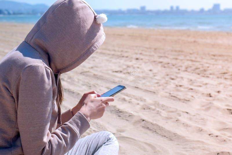 De onherkenbare vrouw typt op telefoon op het strand door overzees royalty-vrije stock afbeelding