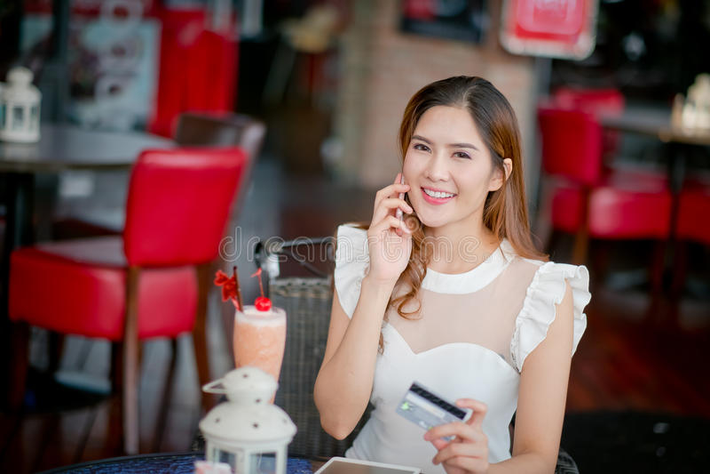 De Online betaling, Meisjes 's handen die een creditcard houden en usin royalty-vrije stock afbeelding
