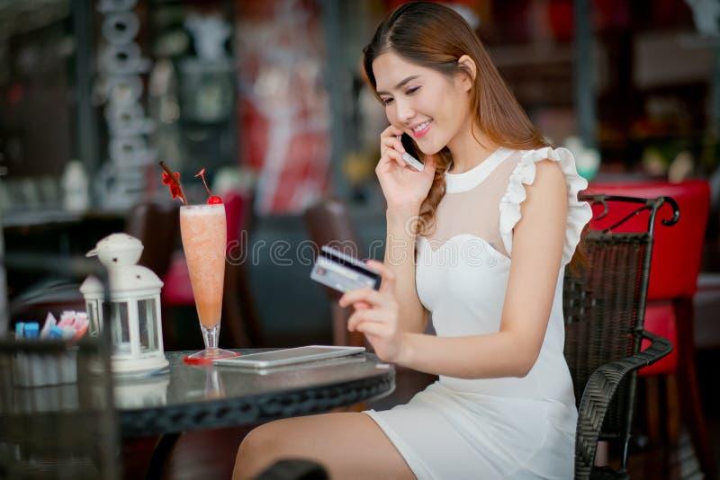 De Online betaling, Meisjes 's handen die een creditcard houden en usin royalty-vrije stock foto