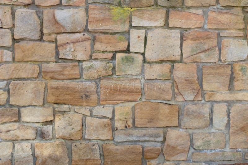 De onregelmatige oude muur van de zandsteen met wat mos stock fotografie