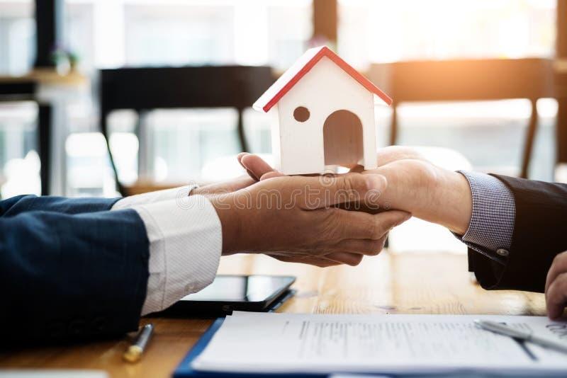 De onroerende goederenmakelaar verklaart contractinvestering alvorens een contractwoonwijk te ondertekenen in bureau contract en  stock foto