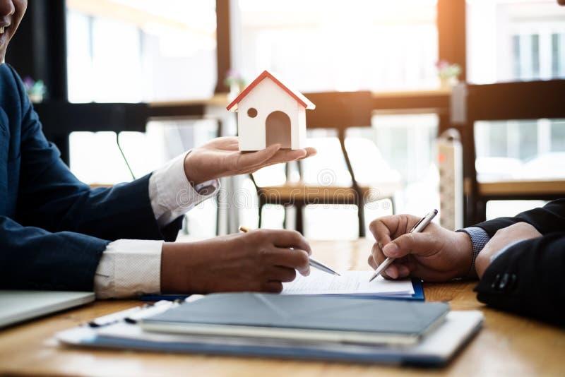 De onroerende goederenmakelaar verklaart contractinvestering alvorens een contractwoonwijk te ondertekenen in bureau contract en  stock afbeelding