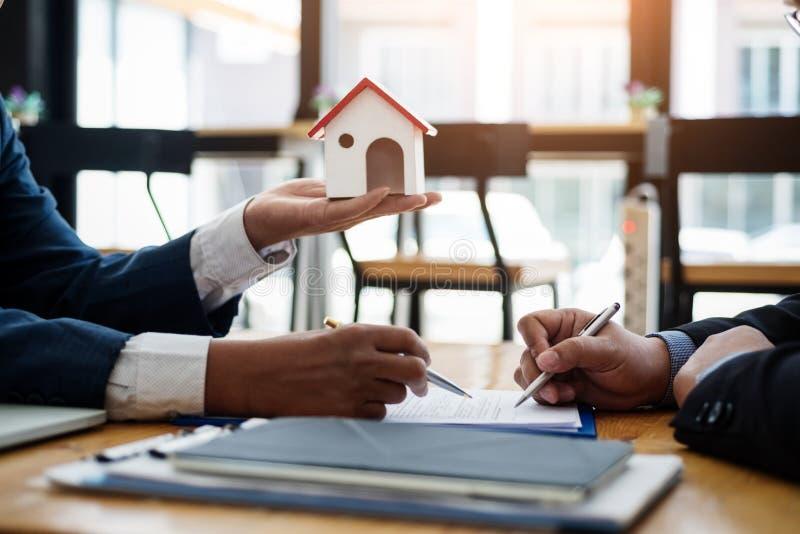 De onroerende goederenmakelaar verklaart contractinvestering alvorens een contractwoonwijk te ondertekenen in bureau contract en  stock foto's