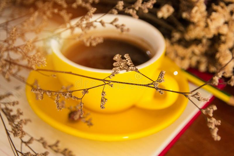 De onscherpe lichte ontwerpachtergrond van gele ceramische koffiekop zette bij de rug van droge bloem, wijnoogst en kunststijl stock foto