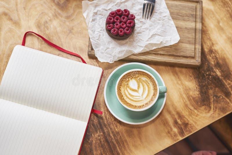De ontbijttijd met kop van verse koffie van hierboven op houten achtergrond, zoete aardbeicake op houten raad, opende uitgespreid stock afbeeldingen