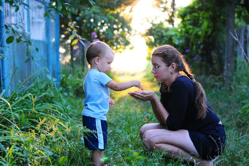 De ontdekking van de kindaard Het kind werpt korrels ter beschikking van moeder Backlit foto's van het kind en de moeder, royalty-vrije stock afbeeldingen