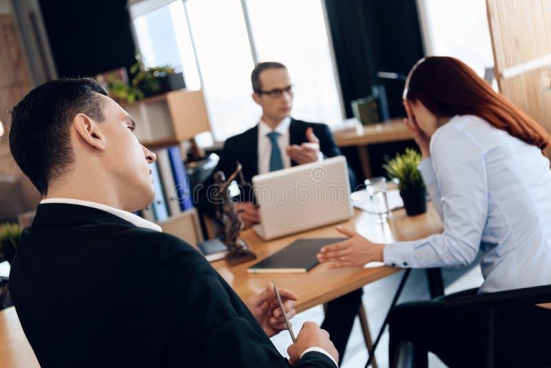 De ontevreden echtgenoot bekijkt gefrustreerde vrouw in het bureau van de scheidingsadvocaat ` s royalty-vrije stock foto's