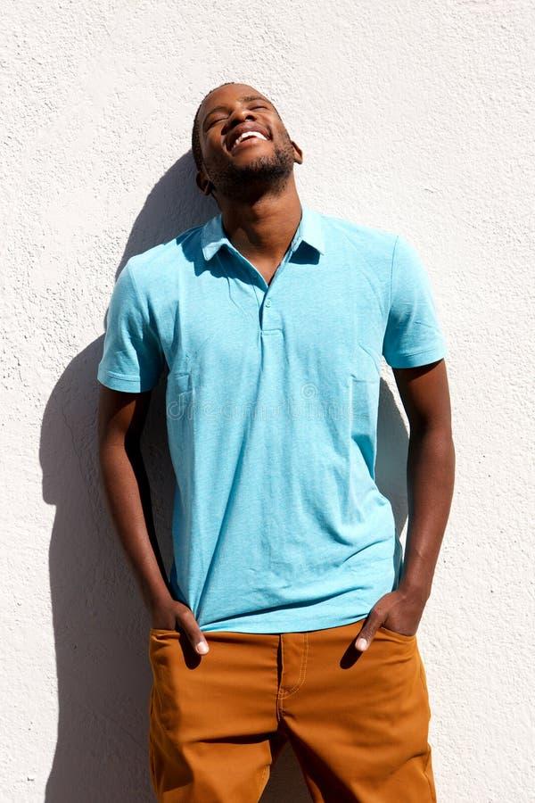De ontspannen jonge Afrikaanse mens die zich met van hem bevinden dient zak in royalty-vrije stock foto
