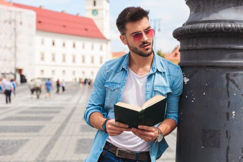 De ontspannen mens die een boek op straat houden kijkt aan kant stock afbeelding