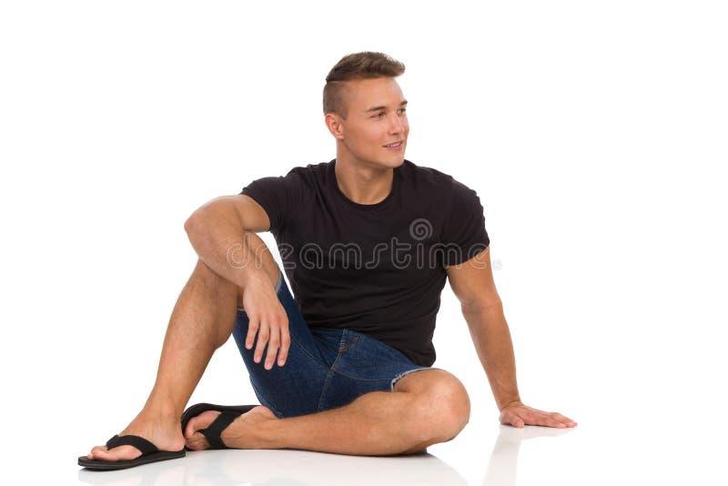 De ontspannen Mens zit op een Vloer en kijkt weg royalty-vrije stock afbeelding