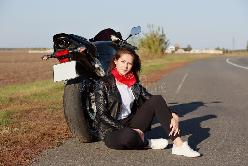 De ontspannen onbezorgde vrouwelijke motorrijder draagt zwarte kleren en de witte trainers, zit bij asfalt dichtbij motor, geniet royalty-vrije stock foto