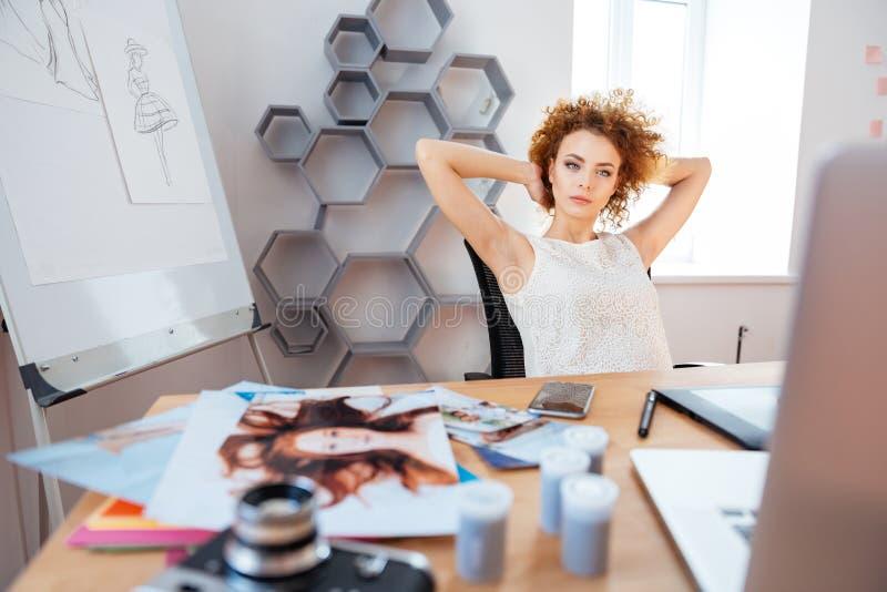 De ontspannen peinzende krullende jonge zitting van de vrouwenfotograaf op werkplaats royalty-vrije stock foto's