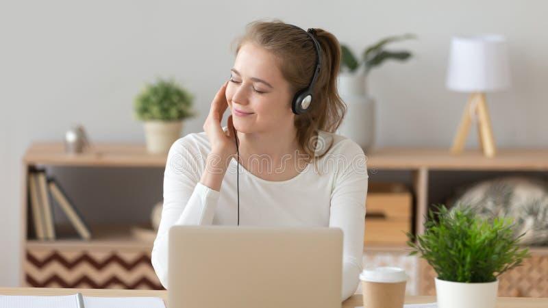 De ontspannen vrouw in hoofdtelefoon luistert aan muziek met gesloten ogen royalty-vrije stock foto's