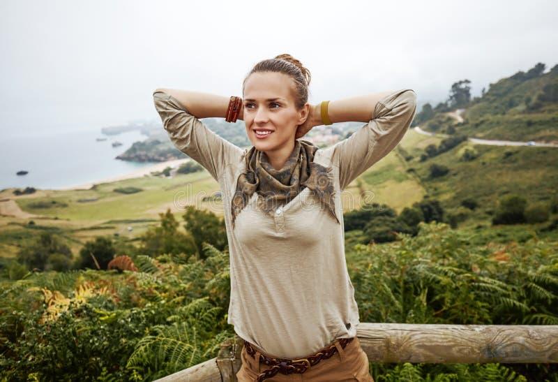 De ontspannen wandelaar van de avonturenvrouw voor oceaanmeningslandschap stock afbeelding