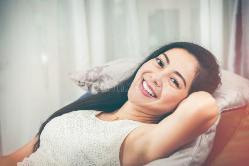 De ontspannende Aziatische vrouw ligt comfortabel en gelukkig glimlachend V royalty-vrije stock foto's