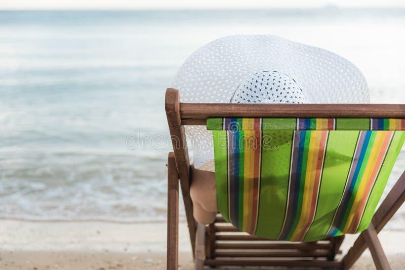 De ontspanning van de de luxereis van het vrouwenmeisje op stoel tropisch strand stock foto