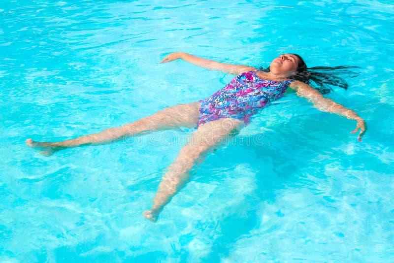 De ontspanningsachtergrond van de de zomervakantie Foto van het mooie donkerbruine vrouw zwemmen op terug in zwembad Tropische to royalty-vrije stock foto