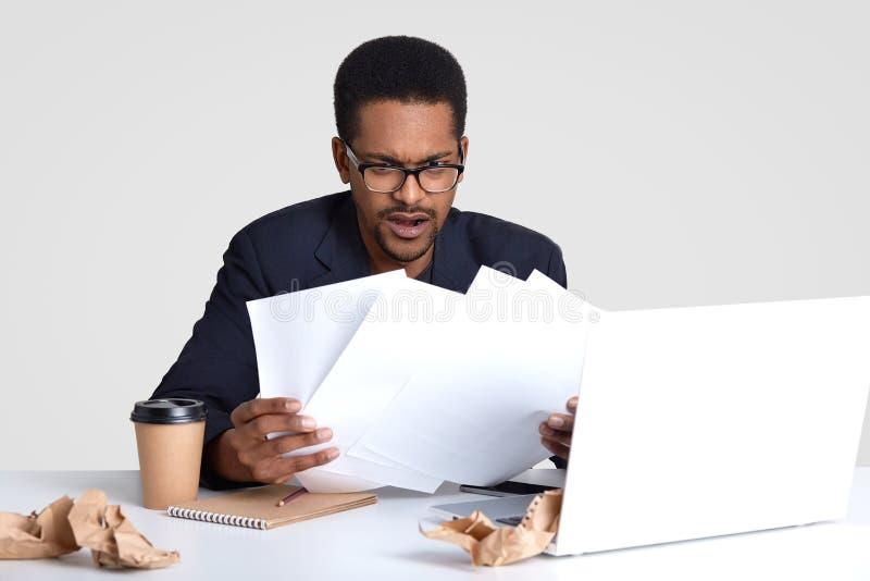 De ontstemde Afrikaanse Amerikaanse mens bekijkt met verwarring document documenten, heeft uiterste termijn om financieel verslag stock afbeelding