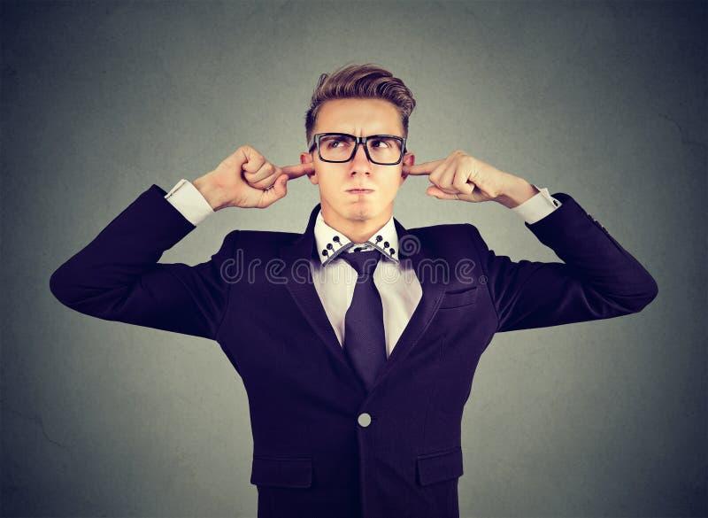 De ontstemde mens die oren met vingers doesn ` t stopt wil luisteren stock foto