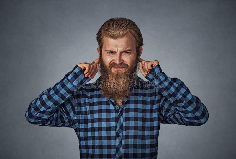De ontstemde mens die oren met vingers stoppen wil niet horen stock fotografie