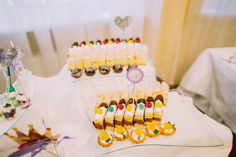 De ontvangst van het desserthuwelijk Heerlijke stukken cakes op de lijst met het teken van het suikergoedbuffet stock foto