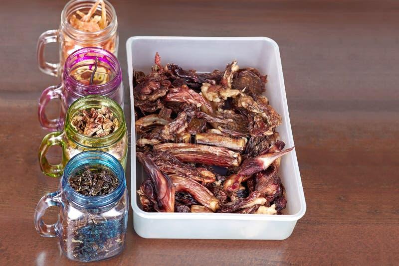 De ontwaterde eigengemaakte vlees en kippenhond behandelt in de potten op houten lijst De hond kauwt beenderen en schokkerig in d stock foto's
