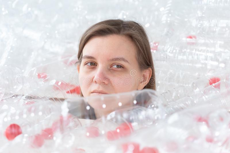 De ontwaterde zieke vrouw ligt in een stapel van plastic flessen Milieuvervuilingprobleem Het huisvuil van de eindeaard stock foto's