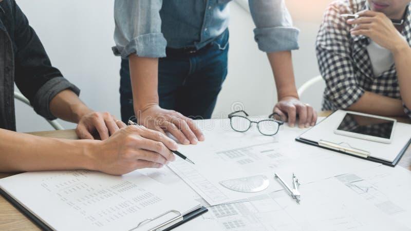 De ontwerpers in het bureau werken de Architect van de Besprekingsblauwdruk aan een nieuw projectontwerp trekken Groepswerk op ho stock foto