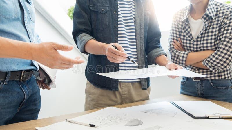 De ontwerpers in het bureau werken de Architect van de Besprekingsblauwdruk aan een nieuw projectontwerp trekken Groepswerk op ho stock afbeeldingen