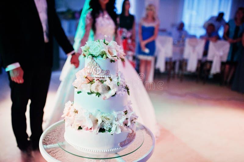 De ontzagwekkende jonggehuwden op huwelijkspartij met huwelijk koeken bij colourfu royalty-vrije stock foto's