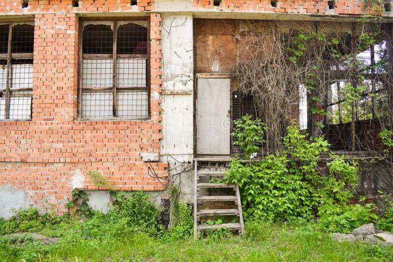 De onvolledige bouw in van de binnenstad Verlaten de bouw project met rode bakstenen en wilde vegetatie stock fotografie
