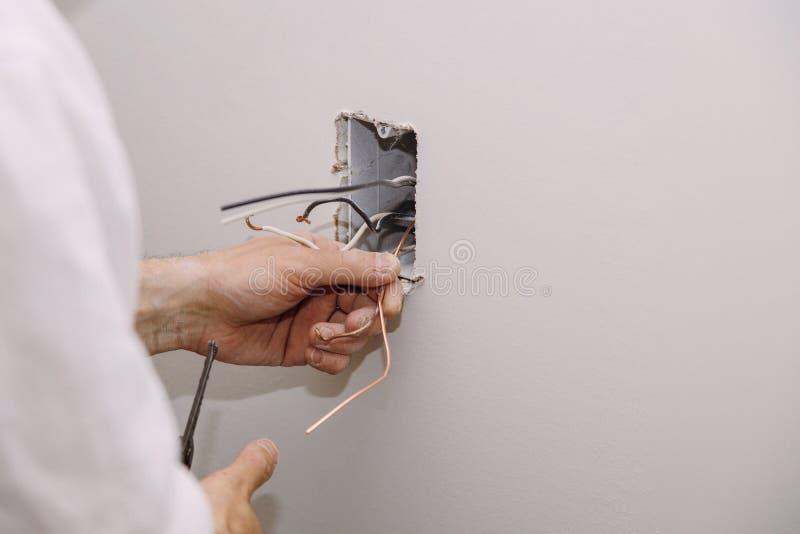 De onvolledige elektrocontactdoos van de leidingenafzet met elektrodraden en schakelaar die in gipsplaatdrywall wordt geïnstallee royalty-vrije stock afbeeldingen