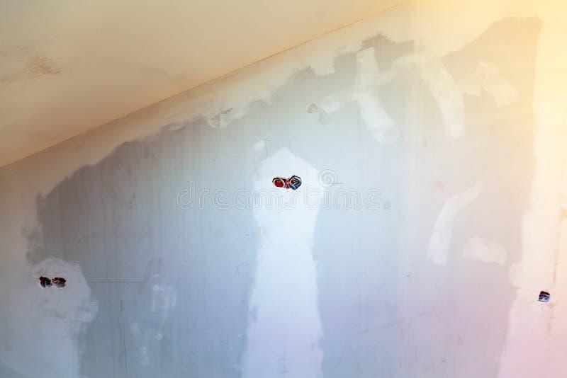 De onvolledige elektrocontactdozen van de leidingenafzet met elektrodiedraden in gipsplaat of drywall voor gipsmuren worden geïns stock afbeelding