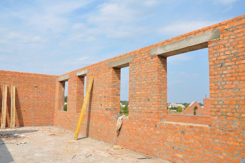 De onvolledige Rode Muur van het Baksteenhuis in aanbouw zonder Dakwerk Zolder het Kaderbouw van de Vensters Concrete Lateibalk royalty-vrije stock fotografie