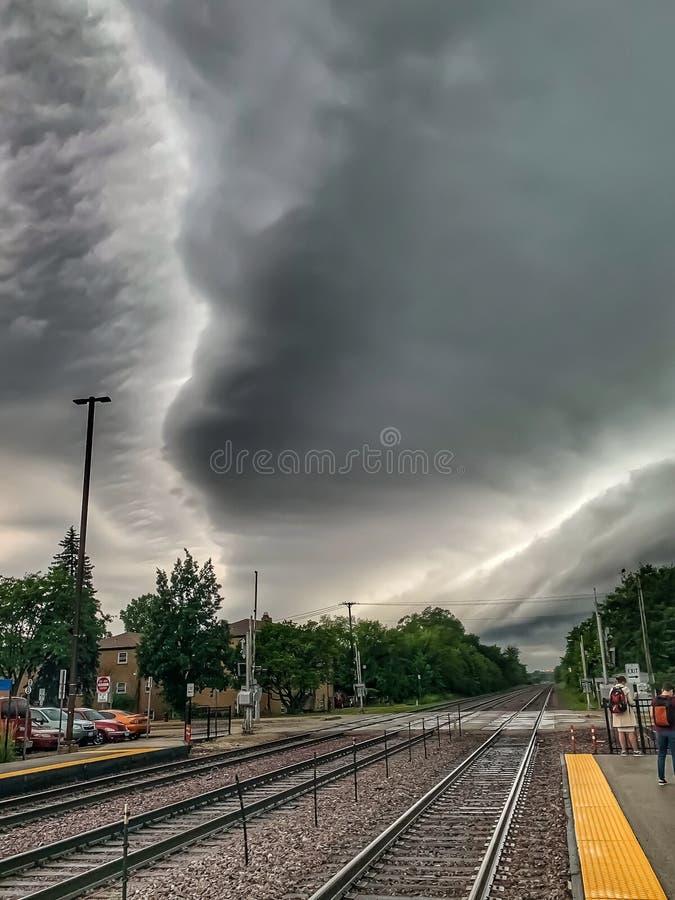 De onweerswolken vormen patronen over metrasporen en stationplatform op het gebied van Chicago stock afbeelding