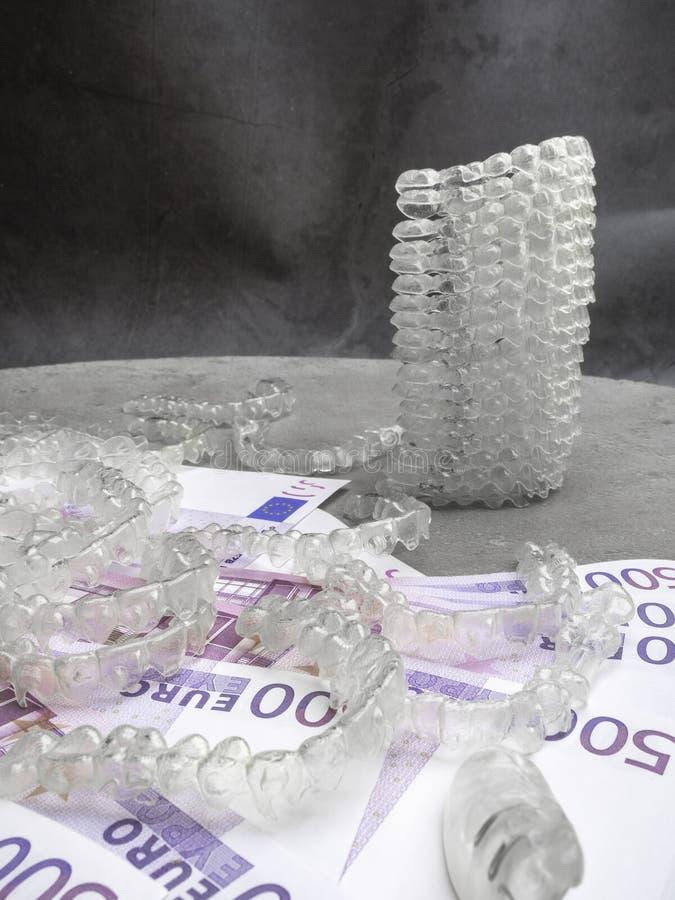 De onzichtbare tandaligners moderne transparante steunen van tandsteunen om tanden en geldcontant geld, kostenconcept recht te ma stock foto